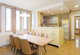 ダイニング・キッチンは2世帯が集まる団らんスペース。レモンイエローの対面カウンターキッチンが空間に明るい雰囲気を演出。家族全員で食事ができる大きなダイニングテーブルは特注のオリジナル。